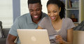 Smiling young black couple using credit card to make online purchases with laptop Royalty Free Stock Photography