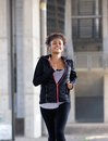 Smiling young black woman running outdoors Royalty Free Stock Photo