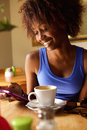 Smiling young black woman using cellphone close up portrait of a at cafe Stock Photo