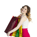 Smiling young blonde girl with colorful shopping bags in white d close up portrait of dress posing on a background Royalty Free Stock Photo