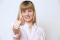 Smiling young blonde woman giving thumbs up. Stock Image