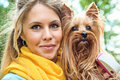 Smiling young blonde with yorkshire terrier outdoor close up portrait Royalty Free Stock Photography