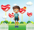 A smiling young boy standing in the garden with giant heart loll illustration of lollipops Royalty Free Stock Images