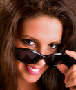 Smiling Young Brunette Looking over Sunglasses Royalty Free Stock Images