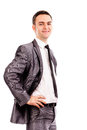Smiling young business man with hands on hips against white background Stock Photography