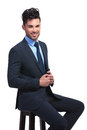 Smiling young business man sitting on a stool white background Stock Photo