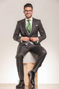 Smiling young business man sitting on wood boxes Royalty Free Stock Photo