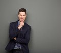 Smiling young business man standing with hand to chin Royalty Free Stock Photo