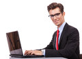 Smiling young business man working at laptop Stock Images