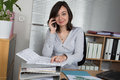 Smiling young business woman on phone taking notes in office Royalty Free Stock Photo