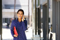 Smiling young business woman talking on mobile phone in the city Royalty Free Stock Photo