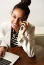 Smiling young business woman using mobile phone and laptop Royalty Free Stock Photo