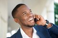 Smiling young businessman calling by mobile phone