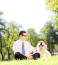Smiling young businessman with his dog sitting on grass in a par park shot tilt and shift lens Royalty Free Stock Photography