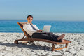 Smiling young businessman lying on a deck chair with his laptop the beach Stock Photography
