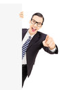 Smiling young businessman pointing with finger behind blank pane panel on white background Royalty Free Stock Image