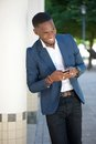 Smiling young businessman sending text message by cellphone portrait of a Royalty Free Stock Image
