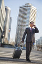 Smiling young Businessman walking down the street with luggage and on the phone Royalty Free Stock Photo