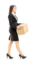 Smiling young businesswoman carrying a box full length portrait of isolated on white background Royalty Free Stock Photo