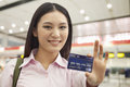 Smiling young businesswoman indoors holding out and showing credit card Royalty Free Stock Photo