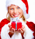 Smiling young christmas woman giving a gift Royalty Free Stock Image