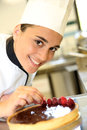 Smiling young confectioner cheerful girl at training school making cake Stock Image