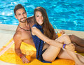 Smiling young couple enjoying a day at the pool tanned healthy in their swimsuits reclining on yellow towel poolside looking up Royalty Free Stock Photos