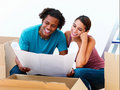 Smiling young couple holding a blueprint Stock Photography