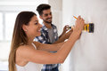 Smiling young couple measuring wall with level tool, renovation Royalty Free Stock Photo