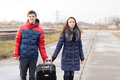 Smiling young couple pulling along a suitcase both holding onto the handle as they walk rural road alongside railway Stock Images