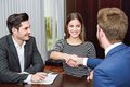 Smiling young couple shaking hands with an insurance agent or investment adviser Royalty Free Stock Photos