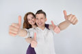 Smiling young couple showing thumbs up