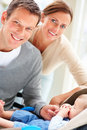 Smiling young couple with their cute newborn baby Stock Photos