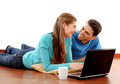 Smiling young couple using laptop at home Royalty Free Stock Photo