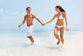 Smiling young couple walking on beach Stock Image