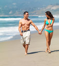 Smiling young couple walking on beach Royalty Free Stock Images