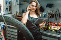 Smiling young craftswoman using gadgets in the repair shop Royalty Free Stock Photo