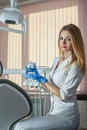 Smiling young dentist keeps toy jaw in cabinet of dental clinic Stock Photos