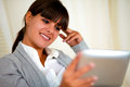 Smiling young female reading on tablet pc screen Royalty Free Stock Photos