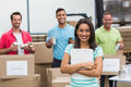 Smiling young female volunteer holding clipboard in a large warehouse Royalty Free Stock Image
