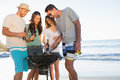 Smiling young friends having barbecue together on the beach Stock Image