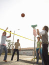 Smiling young friends playing volleyball in street portrait of over police tape Royalty Free Stock Image