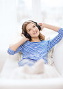 Smiling young girl in headphones at home technology music and happiness concept Royalty Free Stock Image