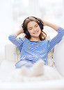 Smiling young girl in headphones at home technology music and happiness concept Royalty Free Stock Photo