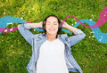 Smiling young girl in headphones lying on grass lifestyle summer vacation technology music and people concept with closed eyes Stock Photography
