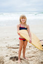 Smiling young girl holding surfboard on beach happy cute with ocean in background Royalty Free Stock Photos