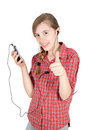 Smiling young girl listening to music on her cellphone and showing thumb up isolated on white background half length studio shot Stock Photography