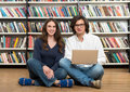 Smiling young girl and young man sitting on the floor in the lib men library with crossed legs men holding a laptop his knees Stock Photography