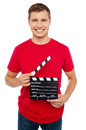 Smiling young guy holding clapperboard Royalty Free Stock Images