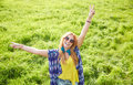 Smiling young hippie woman dancing on green field Royalty Free Stock Photo